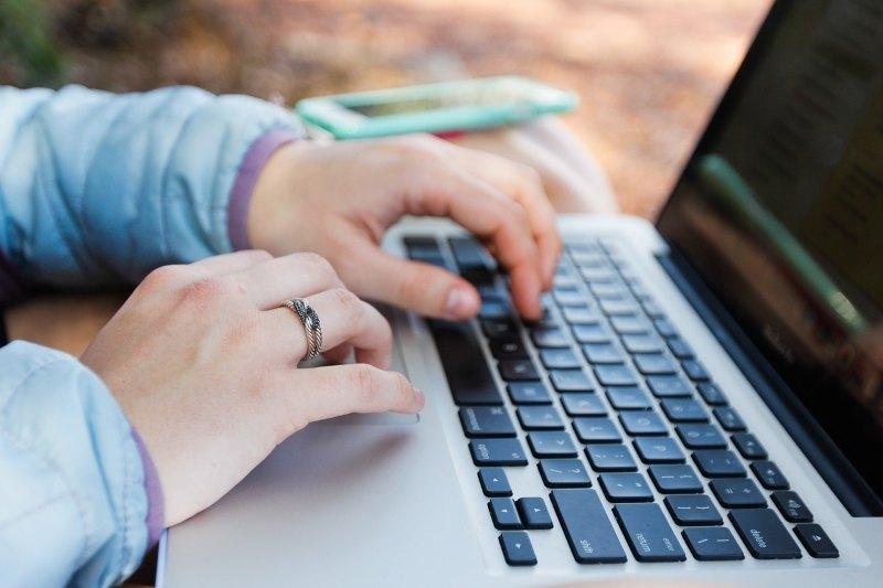 Kannettavan tietokoneen käyttäjä kirjoittamassa